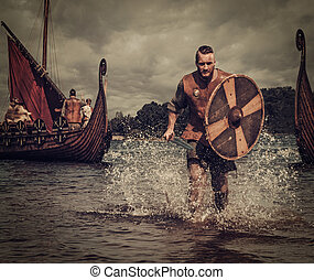 Viking warrior in the attack, running along the shore with...