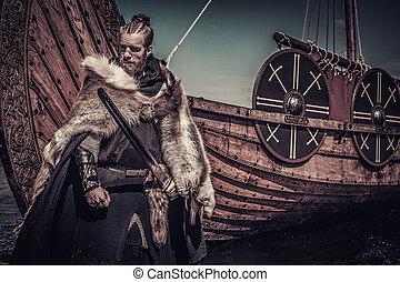 Viking warrior with sword standing near Drakkar on seashore.