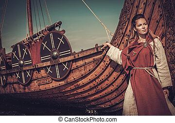 Viking woman standing near Drakkar on the seashore. -...