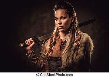 Viking woman with sword in a traditional warrior clothes, ...