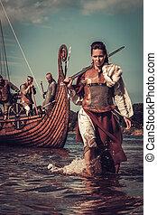 Viking woman with sword walking along the shore with Drakkar...