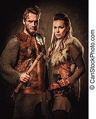 Vikings couple posing in studio on dark background. -...