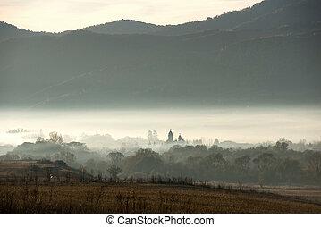 Village church in misty morning lights
