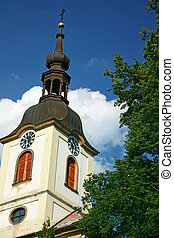 Village church tower with a clock tower. Blue sky with white clouds in the background. (Potstejn, Czech Republic)