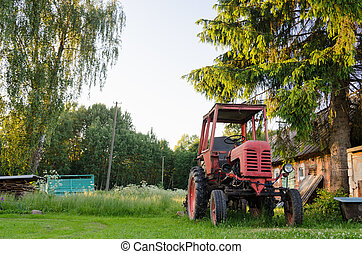village farm red old tractor in meadow summer time