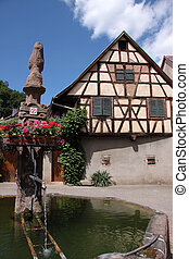 Village fountain with with half-timbered house