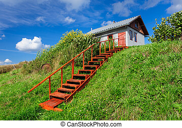 Village house at hill, with stairs