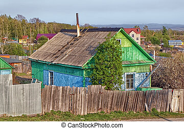 Village house behind the old fence on a sunny summer day