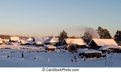 Village houses in winter at sunset. Time Lapse