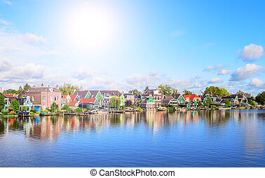Village houses on the river bank in the Netherlands. ...