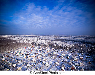 Village in forest. Winter aerial view. Blue cloudy sky.