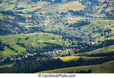 village in sunlit valley view from above. forest with golden...