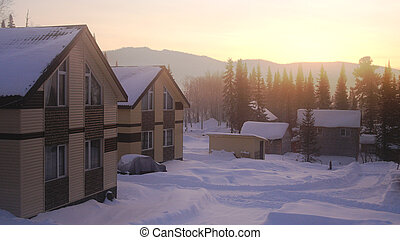 Village in the mountains at amazing sunrise. Fantastic winter landscape. Snowy mountains.