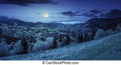 village on mountain slope at night - panoramic landscape of...