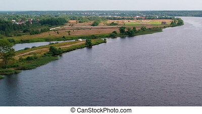 Village on Volga river aerial view from flying quadcopter over forest.