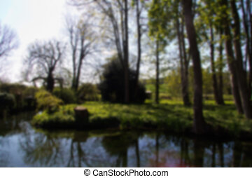 Village pond surrounded by trees in the Chilterns Out of focus.