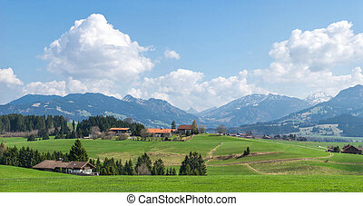 Village surrounded by green forests and snow covered mountains