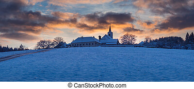 village with a church on a hill at sunset in winter, beautiful sky, Vezovata Plane, Czech republic