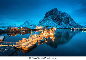 Village with boats on the sea at night and snowy mountains