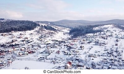 Village with buildings and a visible church all covered with snow. Aerial view