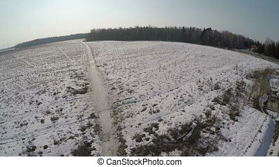 Village with vast snowy fields near the forest, aerial view...