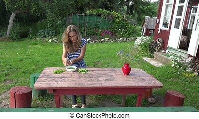 Villager blond girl pod green peas on wooden table near rural house. 4K