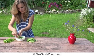 Villager blond girl pod shell green healthy peas on wooden table. 4K