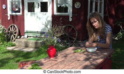 Villager blond woman husk green peas on wooden table near...