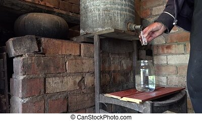 Villager man hands fill glass with home made illegal alcohol...