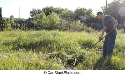 Villager mows the grass in your hand. Traditional metod of...
