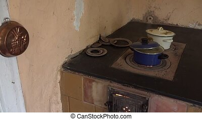 villager woman hands check boiling potatoes on old furnace stove.