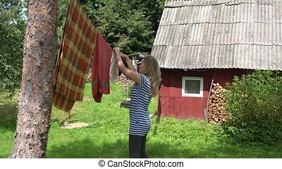 Villager woman hanging washed clothes on clothesline in village. 4K