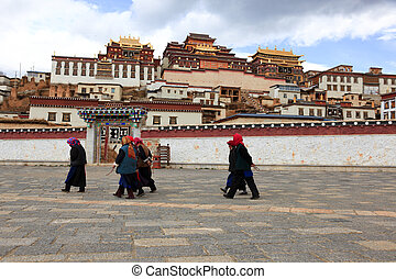 Villagers walking in front of Songzanlin Monastery in Zhongdian (Shangri-La), Yunnan, China