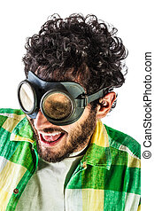 a guy wearing casual clothes and on old pair of goggles over a white bachground