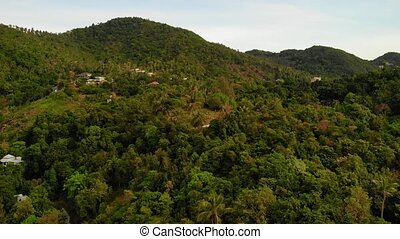 Villas on green mountain ridge. Majestic drone view of luxury villas located on green mountain range on tropical paradise exotic island.
