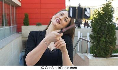 ville, femme, crosse, photo, prendre, smartphone, séduisant, faces, utilisation, elle-même, selfie, confection