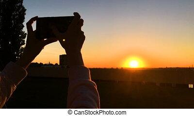 ville, femme, photo, prendre, smartphone, coucher soleil