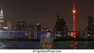 ville, femme, tablette, paysage., contre, toit, nuit, natation, utilisation, vue, piscine, gratte-ciel