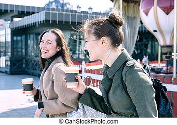 ville, marche, sien, lourdement, rues, ensoleillé, deux, jeune, jour, café, rire, tenant main, femmes, sourire, tasses, heureux