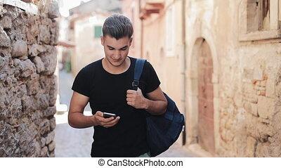 ville, marche, vieux, autour de, backpack., mobile, attentes, jeune, nombre, téléphone, séduisant, réponse, cadrans, homme