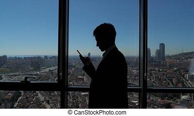 ville, silhouette, téléphone bureau, jeune, panoramique, fenêtre, brouter, homme affaires, vue.