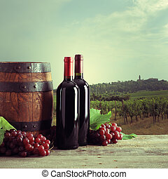 Vineyard - Red wine bottles with barrel and grapes, vineyard...