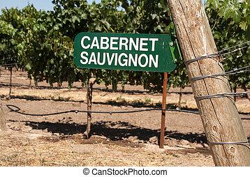 Vineyard sign for Cabernet Sauvignon grapes on the vine