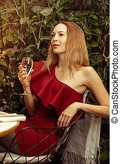 vinho, coquetel, um, jovem, branca, red-burgundy, senta-se, mulher, assimétrico, ombro, vestido, cintilante, bonito, restaurante, vidro