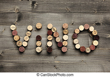 """Vino - """"VINO"""" written with corks on wooden table"""