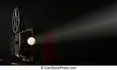 Vintage 16 mm movie projector projecting film in a dark room