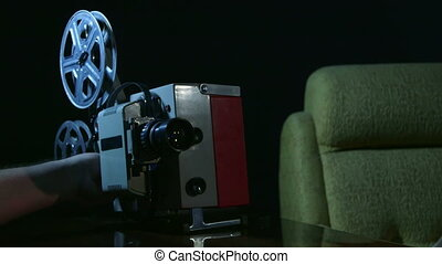 Vintage 16 mm movie projector showing film in a dark room
