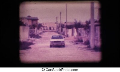 Vintage 8mm. Car driving up a road