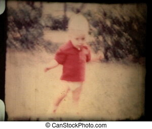 Little boy plays with ball, falling on the ground and laughing. 1960s, vintage 8mm film footage.
