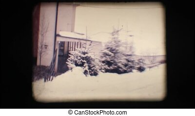 Vintage 8mm. Snowy neighbourhood with cars and trees